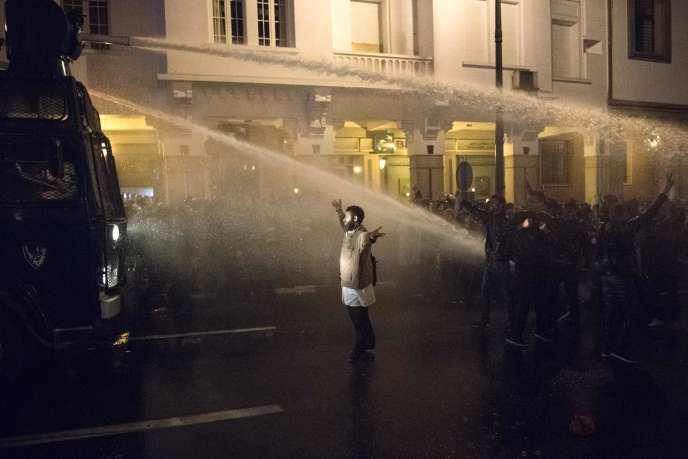 Un manifestant marocain lève les bras devant les canons à eau utilisés par la police lors d'une manifestation dans la capitale Rabat, le 24 mars 2019.