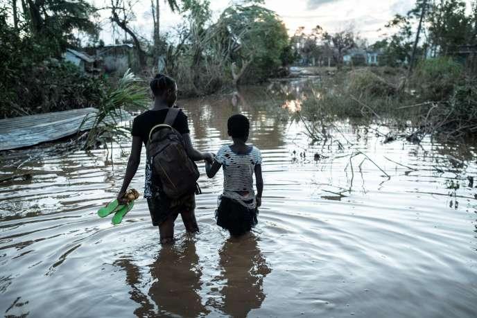 Rosita Zacarias (à gauche), âgée de 15 ans, tient sa jeune soeur de 9 ans,Joaninha, dans les eaux des inondations provoquées par le cyclone Idai, qui a détruit leur maison. Dans le district de Buzi, au Mozambique, le 22 mars 2019.