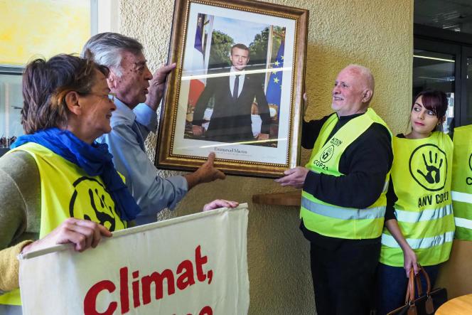 Des militants d'ANV COP21 et le maire de Cabestany (Pyrénées-Orientales), Jean Vila, enlèvent le portrait d'Emmanuel Macron accroché dans la mairie de la ville, le 27 février 2019.