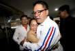 Supporter hugs Palang Pracharat Party leader Uttama Savanayana, right, after press conference at Palang Pracharat Party Bangkok, Thailand, Sunday, March 24, 2019. A military-backed party has taken the lead in Thailand's first election since a 2014 coup, preliminary results showed Sunday, suggesting junta leader and Prime Minister Prayuth Chan-ocha could stay in power.(AP Photo/Sakchai Lalit)
