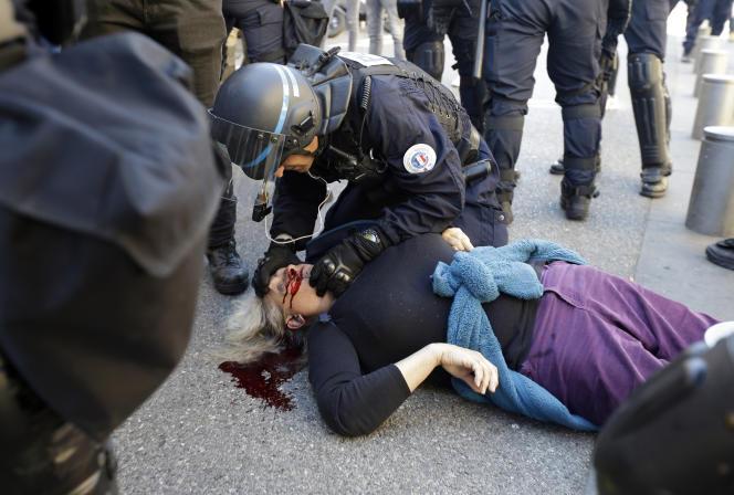 Un policier s'occupe de Geneviève Legay, inconsciente au sol après sa chute, samedi 23mars.