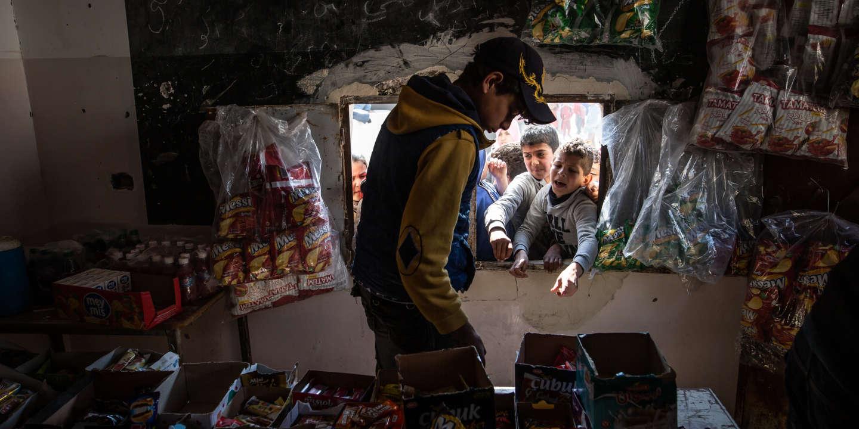 Raqqah, le 10  mars 2019. Ecole Meydan de Raqqah. L'école se situé juste à coté, d'un immeuble qui abritait la police islamique de Daesh( Hisba.) Pendant la récréation, les élèves se bousculent pour acheter leur gouter.