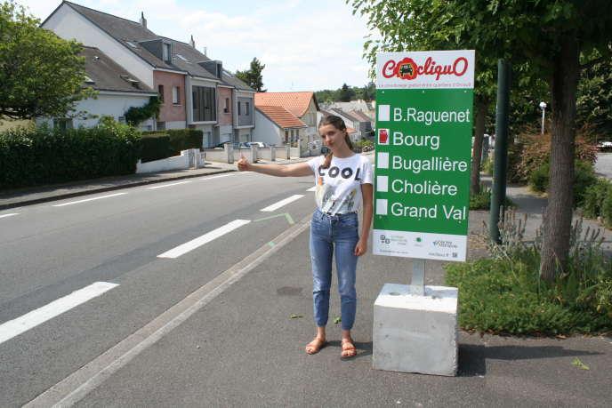 Une jeune femme fait du stop près d'un panneau du réseau Cocliquo, à Orvault (Loire-Atlantique).