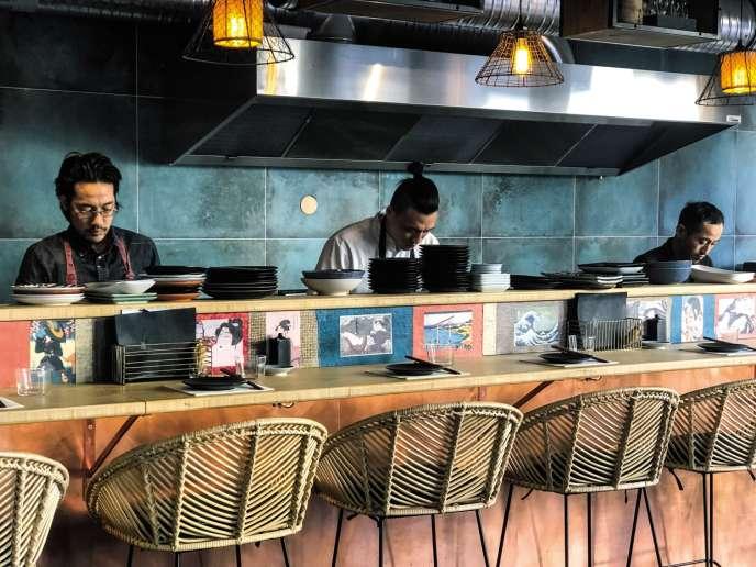 Les cuisiniers japonais derrière le comptoir, dans un décor épuré couleur bleu azur teinte RAL 5009.