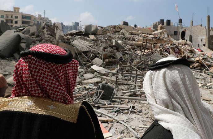 Des Palestiniens se tiennent devant les ruines d'un immeuble du Hamas, après une frappe israélienne, à Gaza-ville, le 27 mars.