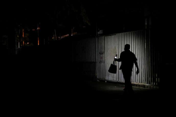 Un habitant de Caracas utilise la lumière de son téléphone portable pour se diriger dans une rue de la capitale vénézuélienne, paralysée par une panne d'électricité, le 26 mars.