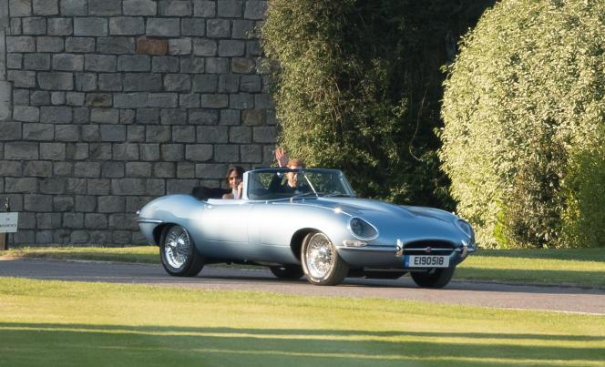 Meghan Markle et le prince Harry, juste après la cérémonie de leur mariage, à bord d'un cabriolet Jaguar Type-E de 1968 équipé d'un moteur électrique, à Windsor (Royaume-Uni), le 19 mai 2018.