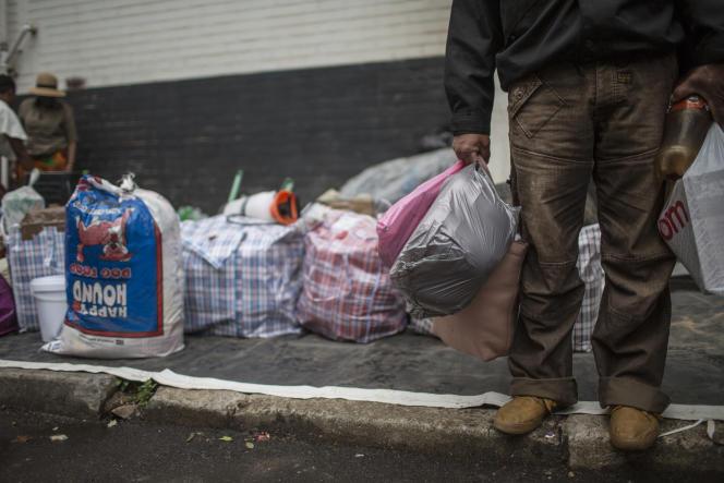 Un «transporteur» attend sur le trottoir de la gare centrale de Johannesburg, en Afrique du Sud, depouvoir embarquer sa marchandise et partir la livrer à plus de 500km de là, au Zimbabwe voisin, en février 2019.