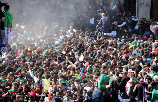 La foule aspergée par un canon à eau utilisé par les forces de l'ordre, à Alger, le 29 mars.