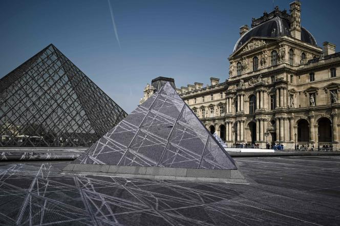 La pyramide du Louvre lors des préparatifs de l'installation de l'artiste JR à Paris, le 28 mars.