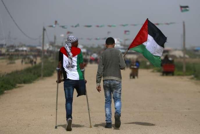 Deux Palestiniens se dirigent vers la manifestation célébrant l'anniversaire de la «marche du retour», à la frontière de Gaza avec Israël, le 30 mars 2019.