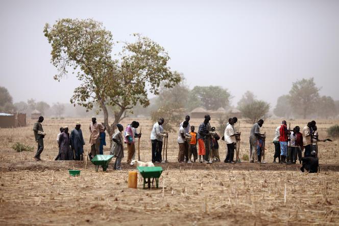 Des paysans construisent des digues pour retenir l'eau près de Diapaga, au Burkina Faso, en mars 2012.