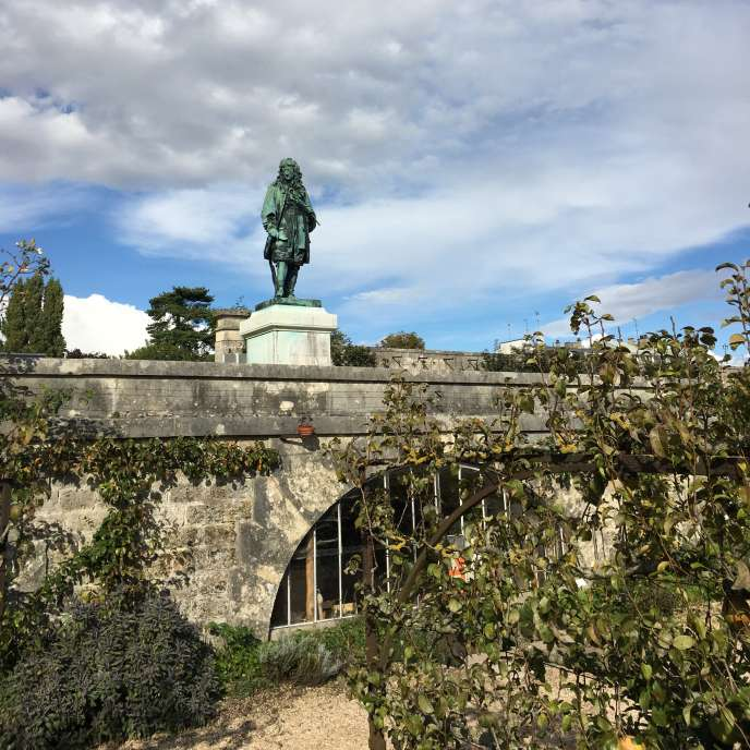 La statue de Jean-Baptiste de La Quintinie vue depuis le Grand Carré, dans le Potager du roi, à Versailles.