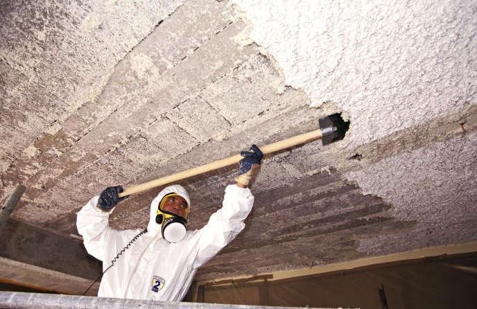 Un ouvrier du bâtiment retire un revêtement d'amiante.