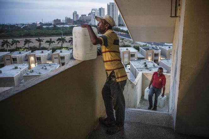 Des habitants transportent des bidons d'eau dans les escaliers du bâtiment San Martin, dans le nord de Maracaibo (Venezuela),le 2 avril.