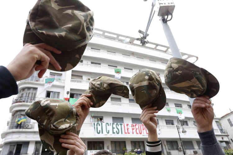 Des membres des forces armées lèvent leurs casquettes, en signe de ralliement au mouvement de protestation.