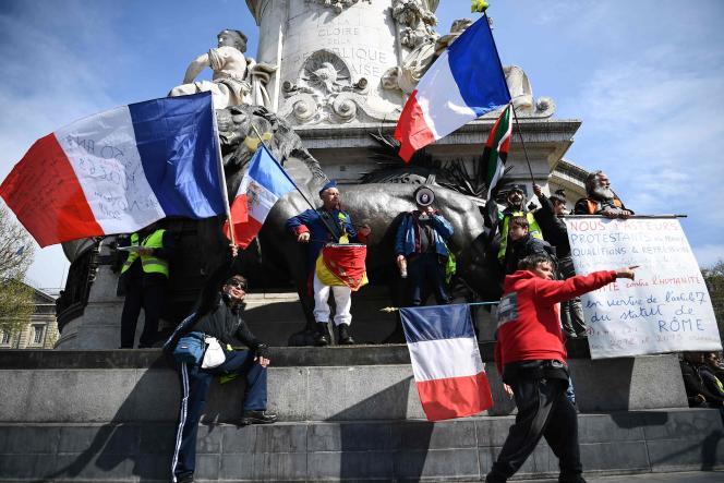 Des « gilets jaunes» devant la statue de Marianne de la place de la République à Paris, le6avril.