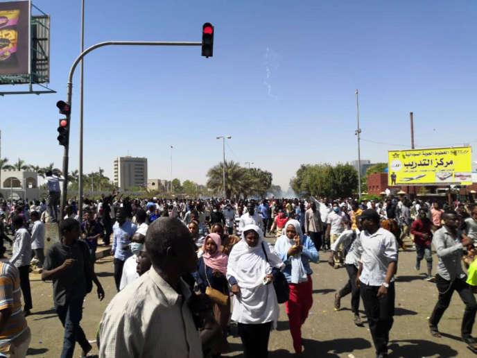 Des manifestants tentent d'éviter le gaz lacrymogène utilisé par les forces de l'ordre près du quartier général de l'armée, à Khartoum, le dimanche 7 avril.