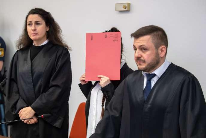 L'accusée, Jennifer Wenisch, se cache le visage derrière une chemise aux côtés de ses avocats, alors qu'elle arrive au tribunal pour l'ouverture de son procès le 9 avril 2019, à Munich (Allemagne).