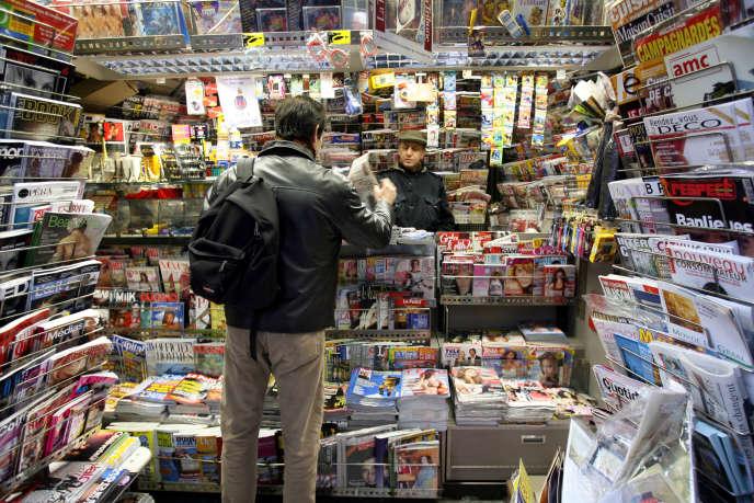 Un homme achète le journal dans un kiosque, à Paris.