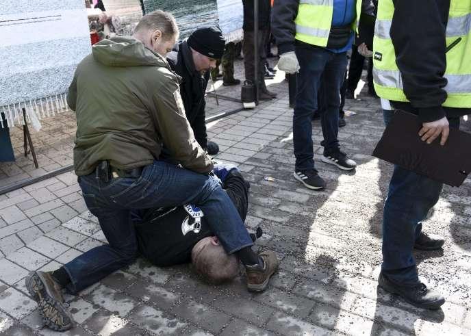 Des agents de sécurité maîtrisent un membre des Soldats d'Odin, un groupe d'extrême droite, en marge d'un meeting de campagne de Timo Soini, à Vantaa, en Finlande, le 24 mars.