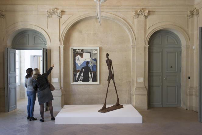 « L'Homme qui marche », de Giacometti (1960), devant « L'Ombre », de Picasso (1953), au Musée Picasso, à Paris, lors de l'exposition « Picasso-Giacometti », en 2016.