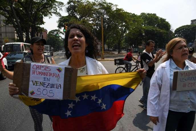 Une supportrice du président par intérim autoproclamé Juan Guaido lors d'une manifestation à Caracas, au Venezuela. Sur sa pancarte, on peut lire « Crise humanitaire au Venezuela, SOS».