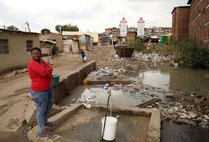 Une femme puise de l'eau dans le township d'Alexandra, à Johannesburg, en Afrique du Sud, le 10 avril.