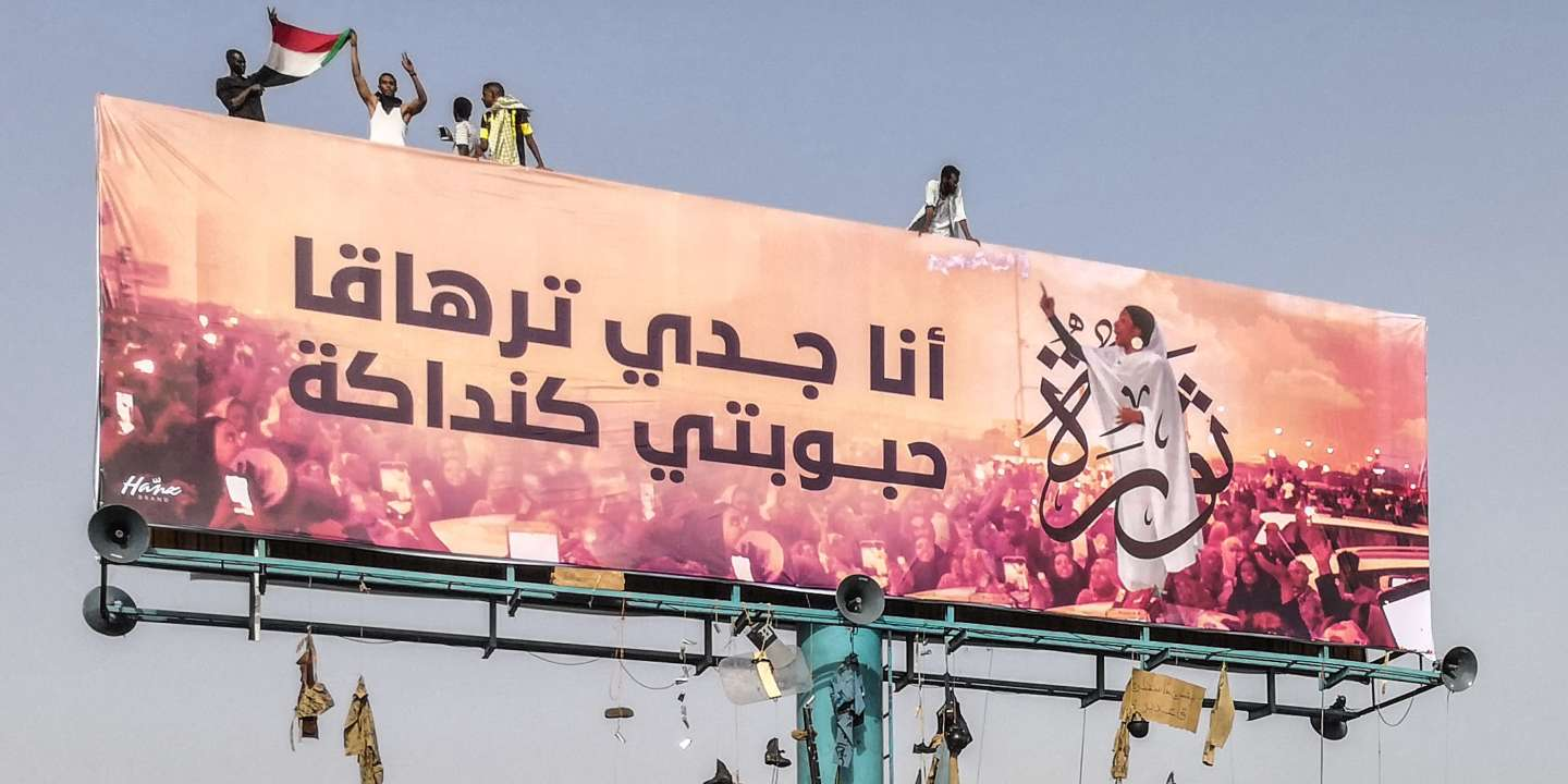 A picture taken during anti-regime protests on April 11, 2019 shows a huge billboard bearing an image of Alaa Salah, a Sudanese woman propelled to internet fame earlier this week after clips went viral of her leading powerful protest chants against Sudan's president, in the Sudanese capital Khartoum. Arabic writing next to her photo in a white gown reads: