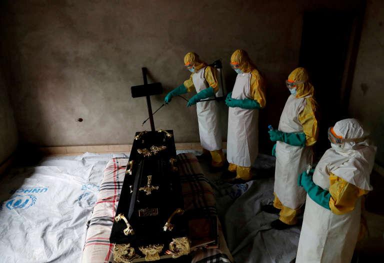 Des agents de santé lors des funérailles d'une personne dont la mort a pu être causée par Ebola, à Beni, en RDC, le 9décembre 2018.