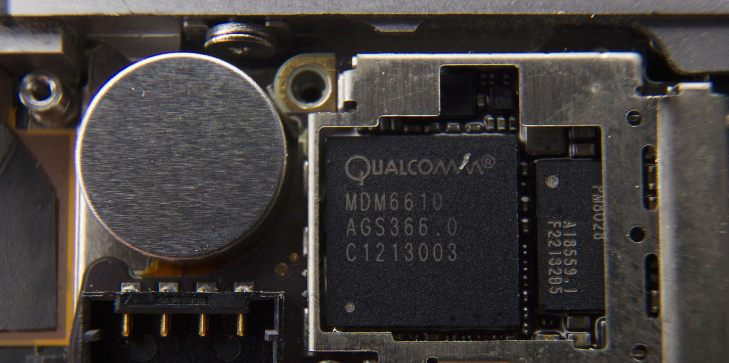 A Qualcomm Inc. baseband processor sits inside a smartphone sold as an Apple Inc. iPhone 4S in an arranged photograph in Hong Kong, China, on Saturday, Jan. 11, 2014. Apple Inc.'s iOS smartphone operating system gained ground in the U.S. in the final quarter of 2013 as the share of the market served by the platforms of Google Inc., Microsoft Corp. and BlackBerry Ltd. shrank. Photographer: Brent Lewin/Bloomberg via Getty Images
