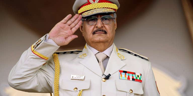 "(FILES) In this file photo taken on May 07, 2018 Libyan Strongman Khalifa Haftar salutes during a military parade in the eastern city of Benghazi during which he announced a military offensives to take from ""terrorists"" the city of Derna, the only part of eastern Libya outside his forces' control. - Forces loyal to Libyan strongman Khalifa Haftar were pushed back on April 5, 2019 from a key checkpoint less than 30 kilometres (18 miles) from Tripoli, checking their lightning advance on the capital, a security source said. (Photo by Abdullah DOMA / AFP)"