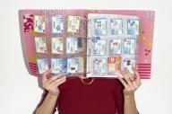 Sarah Guyon pose avec son classeur rempli de bons d'achats, obtenus parfois comme rétribution pour son travail en ligne, le 9 avril.