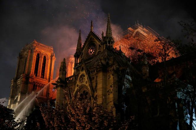 Les pompiers de Paris pulvérisent de l'eau pour éteindre les flammes qui ravagent la cathédrale Notre-Dame de Paris, le 15 avril.