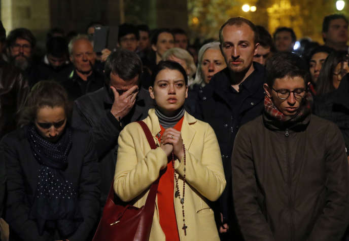 Des personnes se sont réunies pour prier en assistant à l'incendie de Notre-Dame de Paris, le 15 avril.