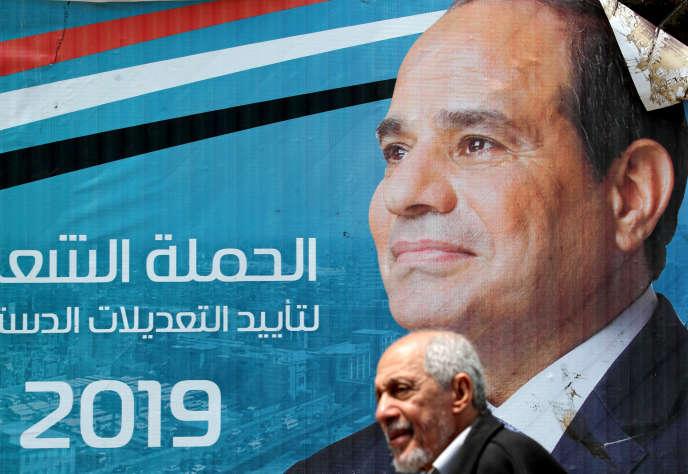 Un homme marche devant une banderole représentant le président égyptien Sissi, le 16 avril 2019, au Caire.