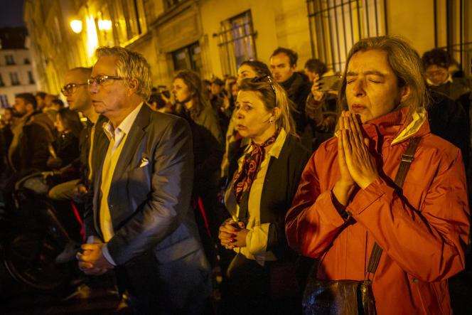 Un groupe de chrétiens prie et chante devant la cathédrale Notre-Dame de Paris, lundi15avril.