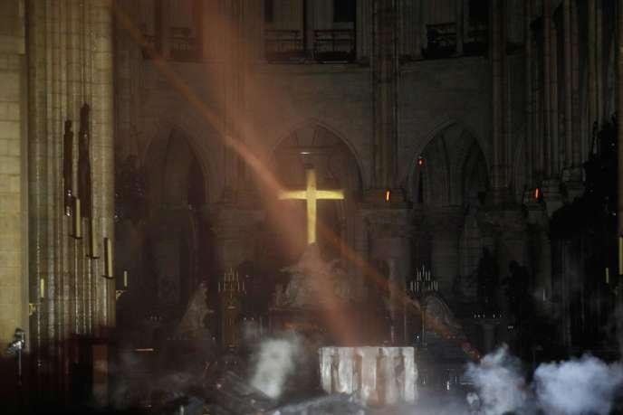 La fumée enveloppe l'autel où trône la croix, à l'intérieur de Notre-Dame de Paris, après l'incendie qui a ravagé la cathédrale, mardi 15 avril 2019.