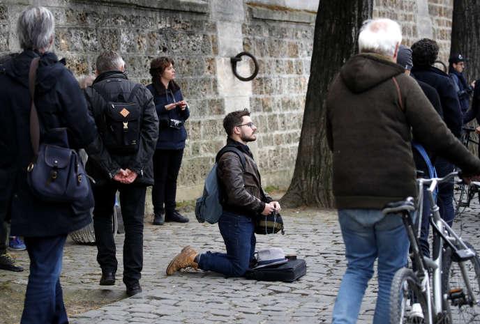 Une personne prie, sur un quai de la Seine, face à cathédrale Notre-Dame, partiellement détruite, le 16 avril 2019.