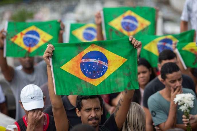 Des drapeaux brésiliens tachés de rouge - comme du sang - aux funérailles d'Evaldo dos Santos Rosa, à Rio de Janeiro (Brésil), le 10 avril.