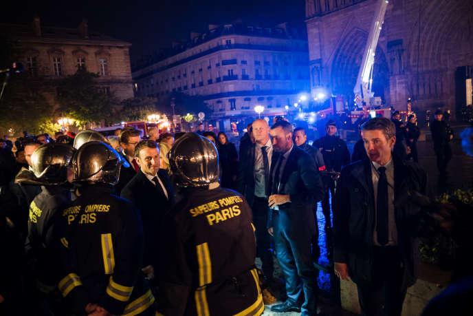 Le président Emmanuel Macron salue des sapeurs pompiers sur le parvis de la cathédrale, dans la nuit du 15 au 16 avril 2019.