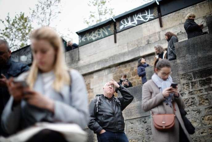 Des gens se sont réunis sur les quais de Seine devant la cathédrale Notre-Dame, mardi 16 avril.