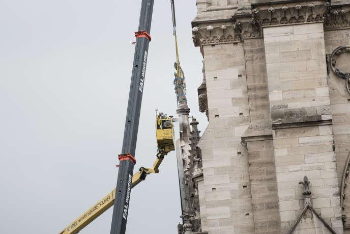 Depuis une nacelle, un ouvrier découpe le socle sous une statue sur le flanc nord de la cathédrale, le 16 avril.