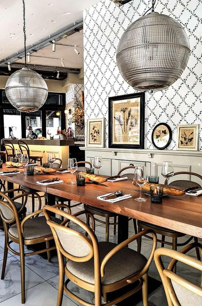Chez Mamie, il y a une grande table d'hôtes en bois, un papier peint printanier, des luminaires chinés, des planches d'herbier mises sous cadre.