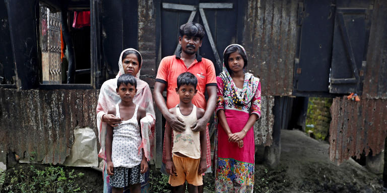Riyazul Haq (C), his son Sahil Shaikh (C-foreground) and his daughter Rimpi Khatun (R) whose names are excluded from the draft list of the National Register of Citizens (NRC), pose for a picture with other family members inside their home in Dhubri district, in the northeastern state of Assam, India August 3, 2018. Picture taken August 3, 2018. REUTERS/Adnan Abidi - RC1F77C002D0