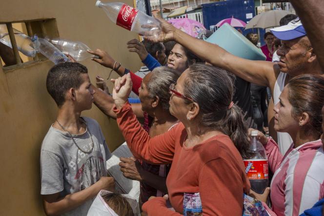 Des habitants de Cabimas font la queue pour remplir leurs bouteilles d'eau, le 2 avril.