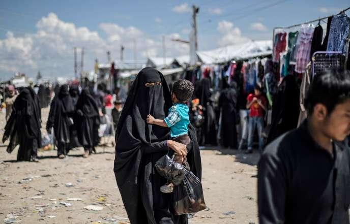Une femme déplacée de la province de Deir ez-Zor, dans l'est de la Syrie, porte un enfant alors qu'elle se promène dans le camp de personnes déplacées d'Al-Hol, dans le gouvernorat d'Al-Hasakeh, dans le nord-est de la Syrie, le 18avril2019. Délogées lors d'une dernière offensive menée par une force terrestre dirigée par les Kurdes et des frappes aériennes de la coalition, des milliers d'épouses et d'enfants de combattants de l'Est ont envahi un groupe de villages syriens au sud du camp d'Al-Hol au cours des derniers mois. Parmi les nombreux Syriens et Irakiens, quelque 9 000étrangers sont détenus dans une section clôturée du campement, sous la surveillance des forces kurdes.