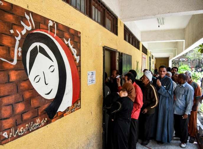 Les Egyptiens attendent pour rentrer dans un bureau de vote situé dans une école cairote, le 20 avril.