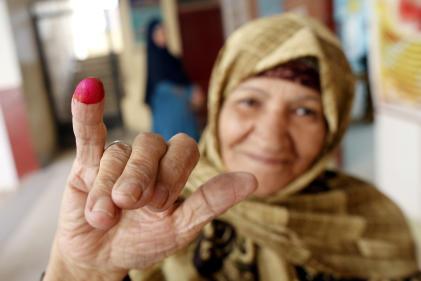 Les personnes ayant voté doivent tremper le doigt dans de l'encre rose.