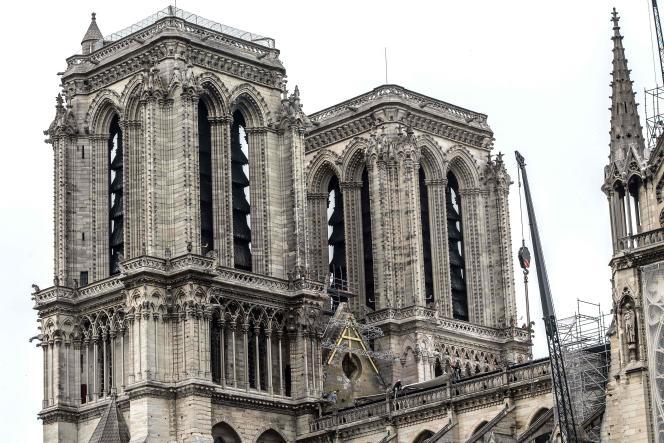 Des ouvriers sont en train d'installer des bâches provisoires pour protégerle chœur, la nef et le transept de Notre-Dame de Paris, le 23 avril 2019.
